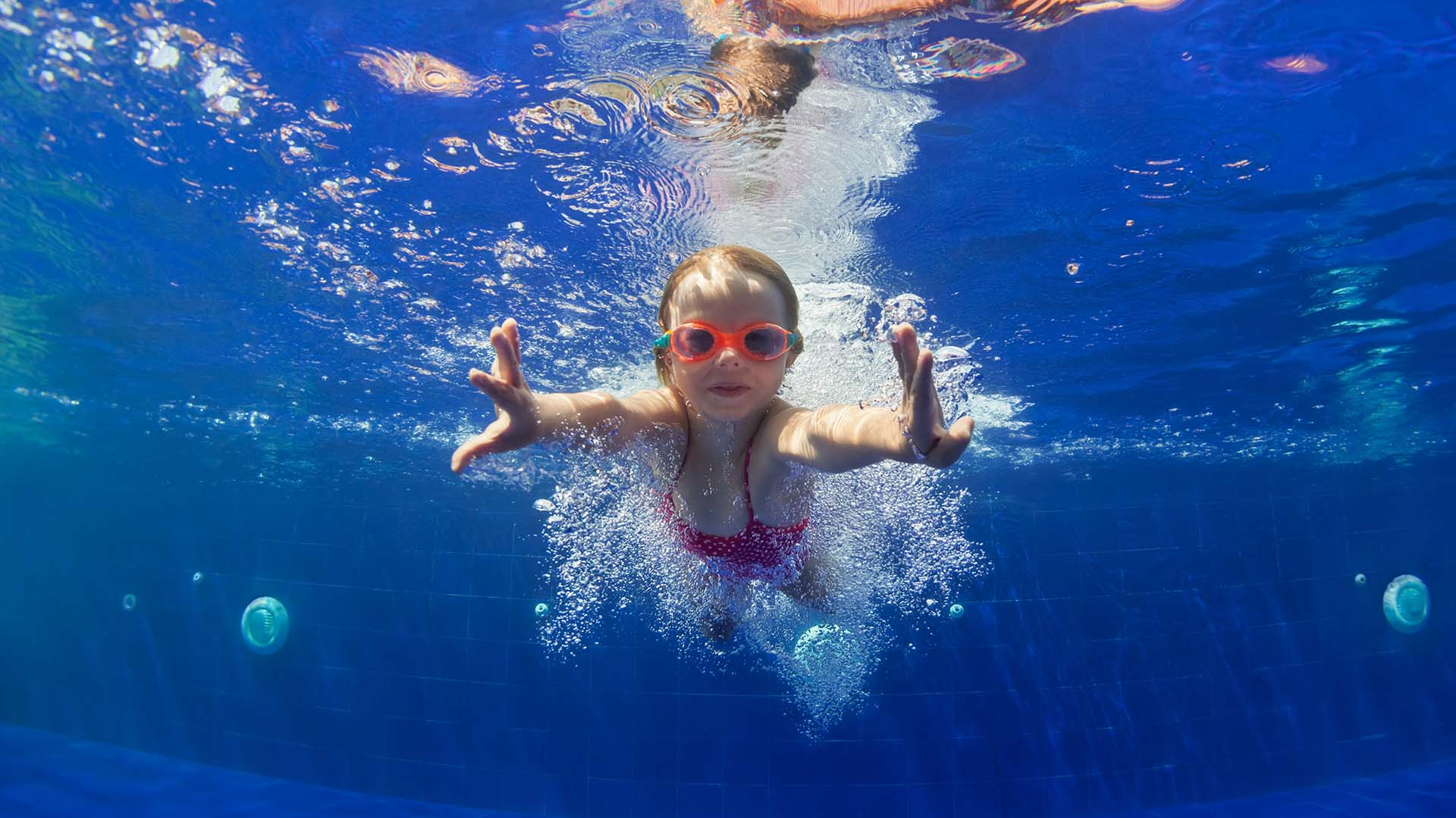 Child swimming in clean blue pool