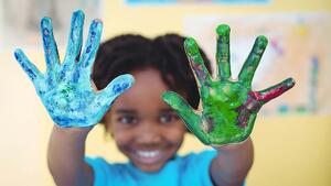 Child with finger paints on hands